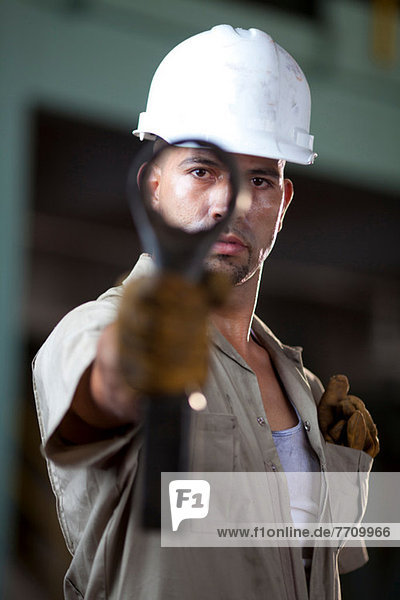 Industrial worker holding tool in plant