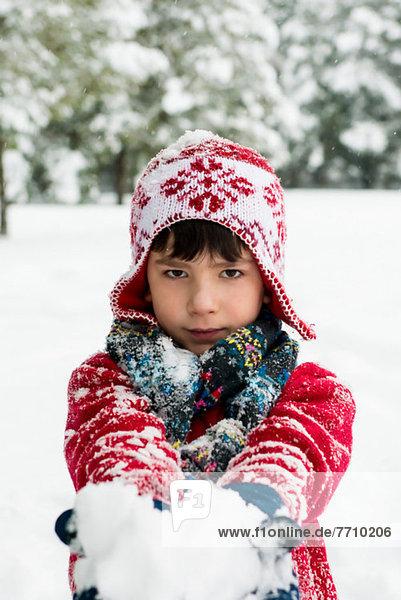 Junge mit Schneeball im Freien