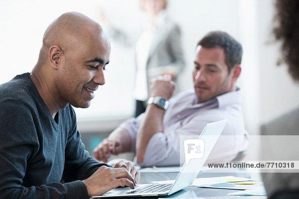 Businessman using laptop in meeting