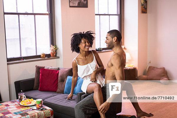 Paar sitzend auf Sofa im Wohnzimmer