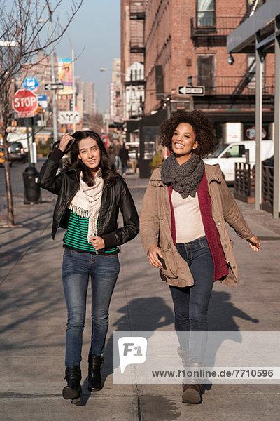 Frauen  die zusammen auf der Stadtstraße spazieren gehen