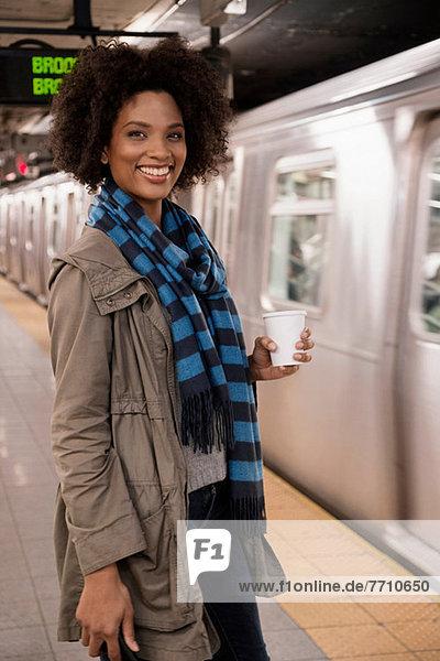 Frau beim Kaffee in der U-Bahn-Station