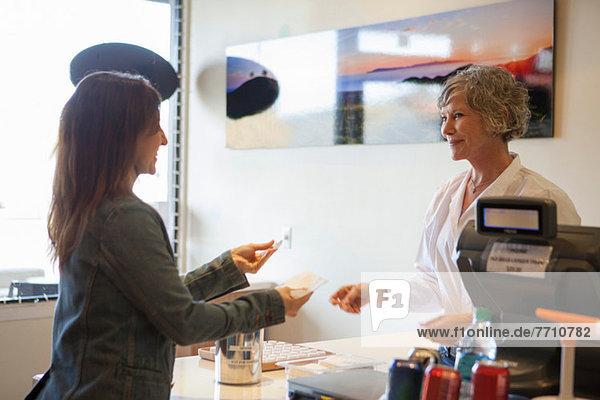 Kassierer im Gespräch mit dem Kunden im Geschäft