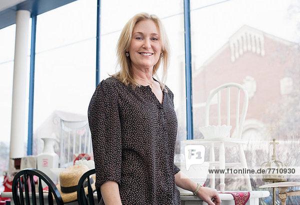 Frau lächelt im Gebrauchtwarenladen