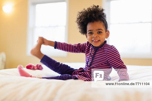 Mädchen spielt auf dem Bett