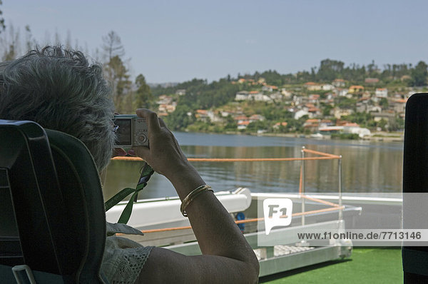 A Woman Passenger River Cruise Takes A Photograph Of The Scenery