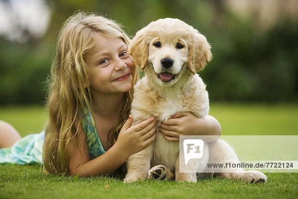 Hawaii  Maui  Little Girl Sits On Grass Holding A Golden Retriever Puppy.