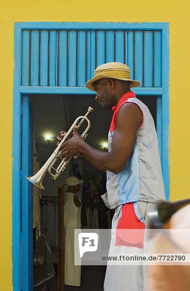 A Street Entertainer Playing A Trumpet Beside Colorful Doorway  Havana  Cuba