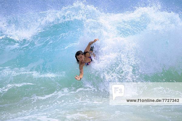 Hawaii  Oahu  Sandy Beach  Woman Bodysurfs In Turbulent Turquoise Ocean