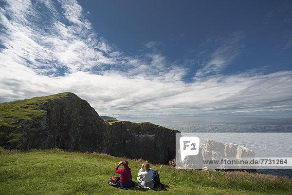 Two People Sitting On The Grass Looking Through Binoculars At The Rocky Promontory At St. Abb's Head  Scottish Borders Scotland