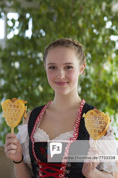 Teenagerin im Dirndl mit Waffeln  Lichtenau  Baden-Württemberg  Deutschland  Europa