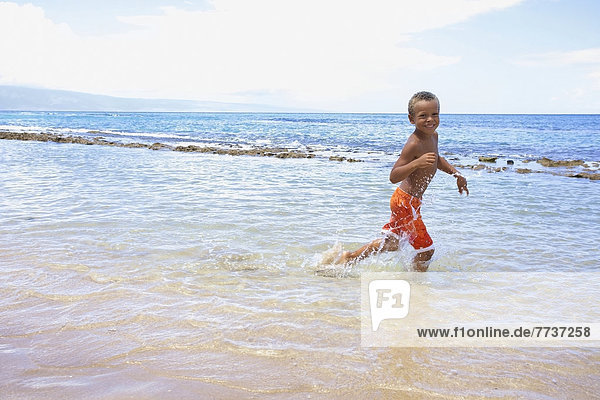 A young boy runs and plays in the shallow water of the ocean Hawaii united states of america