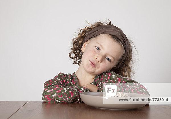 Mädchen sitzt hinter Teller mit Haferflocken