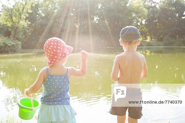 Kinder spielen am See