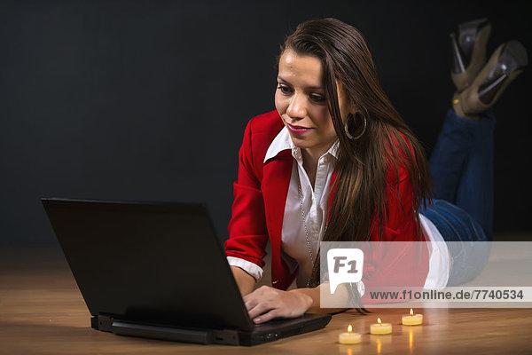 Junge Frau auf dem Boden liegend und mit Laptop bei Kerzenlicht