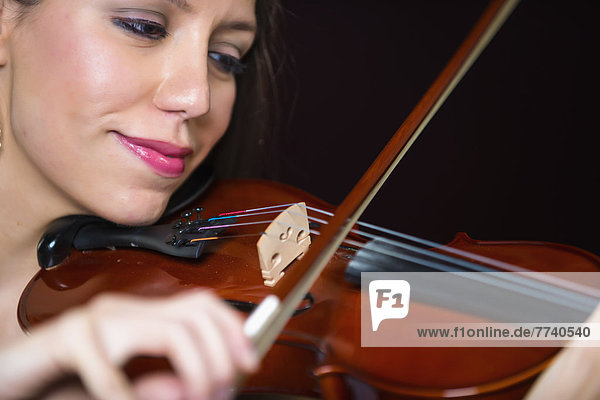 Young woman playing violin  smiling