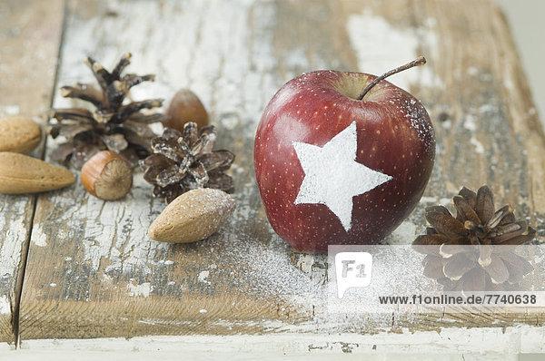 Weihnachtsapfel mit Schneestern  Pinienzapfen  Mandeln und Haselnüssen auf dem Tisch