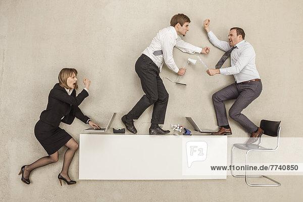 Geschäftsleute kämpfen auf dem Schreibtisch