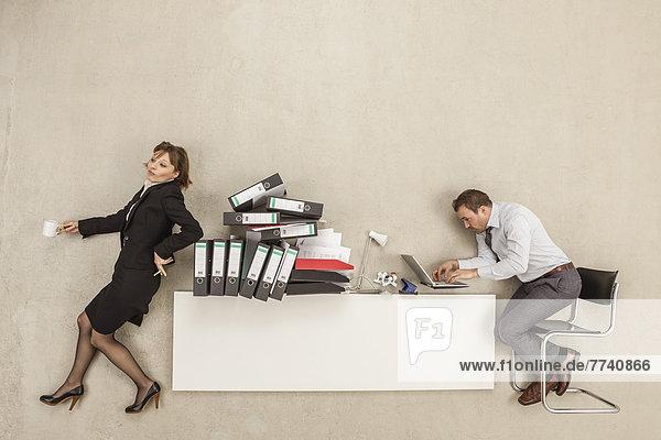 Geschäftsmann  der am Schreibtisch arbeitet  während die Geschäftsfrau sich auf einen Aktenstapel stützt.
