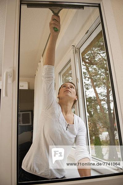 Junge Frau beim Fensterputzen