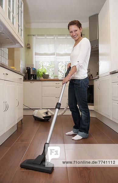 Junge Frau putzt Boden mit Staubsauger