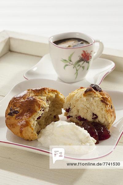 Cranberry Scones mit Schlagsahne und Tasse Kaffee im Tablett  Nahaufnahme