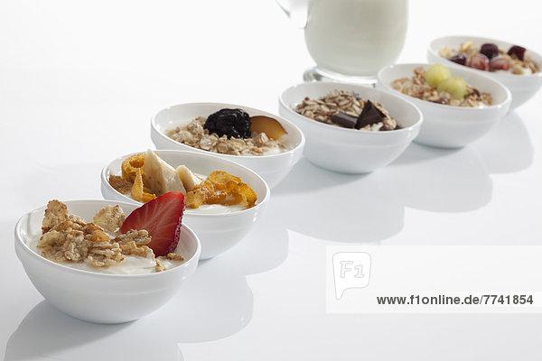 Joghurtschalen mit Müsli und Früchten auf weißem Hintergrund  Nahaufnahme