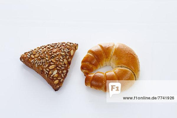 Croissant und Getreidebrot auf weißem Grund  Nahaufnahme