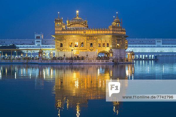 Inderinnen  Pilgerinnen in bunten Saris sitzen am Rand des Wasserbeckens des Amrit Sagar oder Heiliger See  am Hari Mandir oder Goldener Tempel  Hauptheiligtum der Sikh-Religionsgemeinschaft