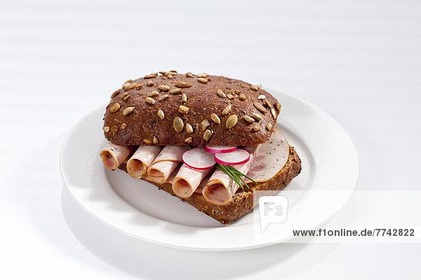 Sandwich aus Vollkornbrötchen mit Geflügel und Kräuterkuchen auf Teller  Nahaufnahme
