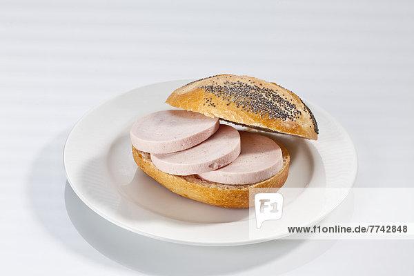 Sandwich aus Mohnbrötchen mit Schinkenwurst auf Teller Nahaufnahme