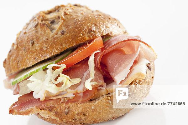 Sandwich aus Kornbrötchen mit Speck auf weißem Grund  Nahaufnahme