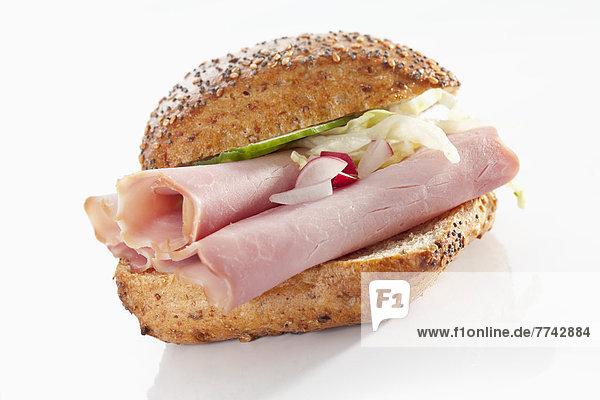 Sandwich aus Vollkornbrötchen mit Schinken auf weißem Grund  Nahaufnahme
