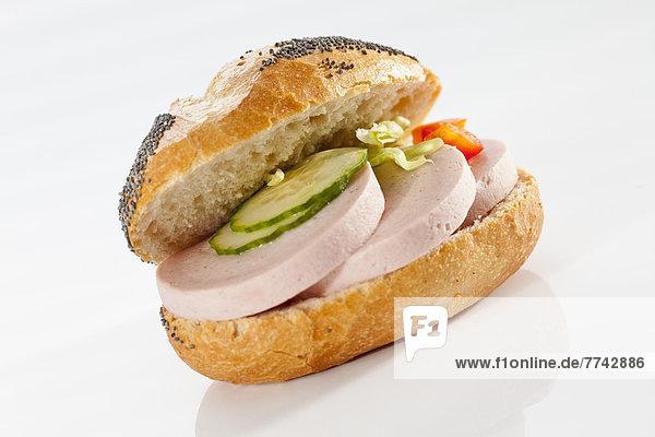 Sandwich aus Mohnbrötchen mit Schinkenwurst auf weißem Grund  Nahaufnahme