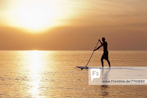 Deutschland  Schleswig-Holstein  Mann auf Stehpaddelbrett auf der Ostsee