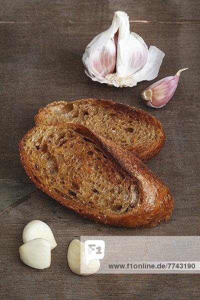 Gebratenes Brot mit Knoblauch auf Holztisch  Nahaufnahme