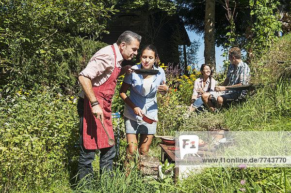 Österreich  Salzburger Land  Mann kocht für seine Familie im Garten