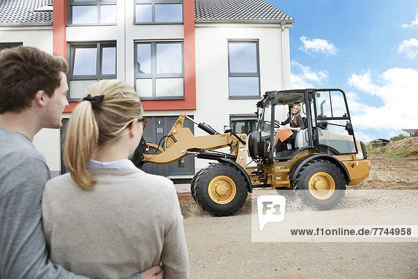 Deutschland,  Neuss,  Immobilienmakler mit Radlader auf der Baustelle,  Paarwartehaus