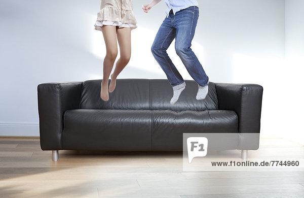 Paar-Springen auf schwarzer Ledercouch