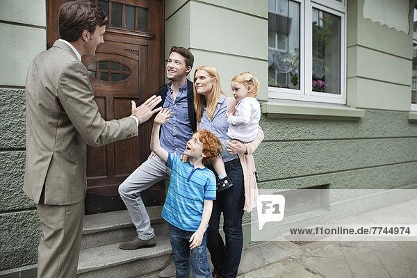 Junge  der dem Immobilienmakler und der Familie  die im Hintergrund stehen  High Five gibt.