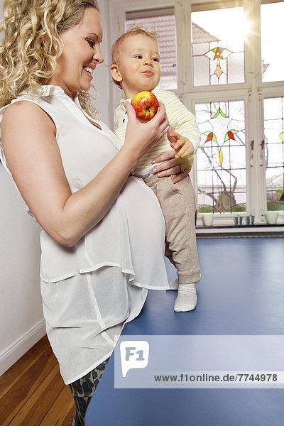 Deutschland  Bonn  Schwangere Mutter isst Apfel mit Sohn im Wohnzimmer  lächelnd