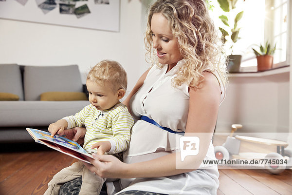 Germany  Bonn  Pregnant mother reading book to son in living room
