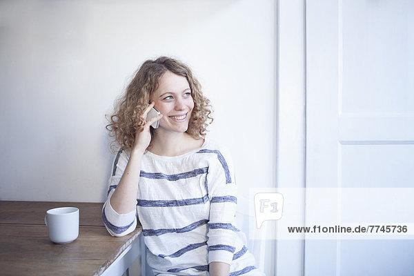 Junge Frau sitzt am Tisch und redet auf dem Handy und lächelt.