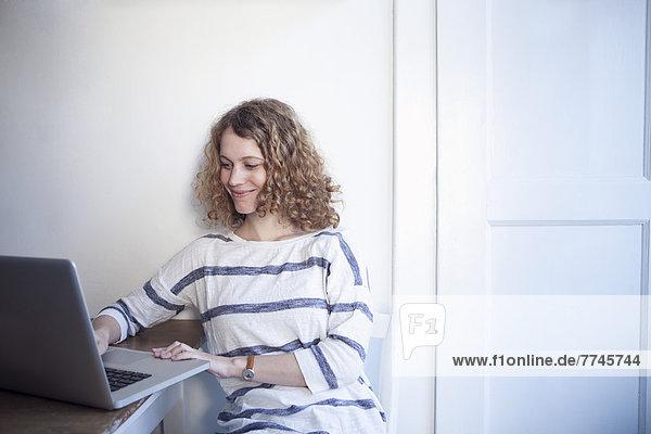 Junge Frau mit Laptop in der Küche  lächelnd