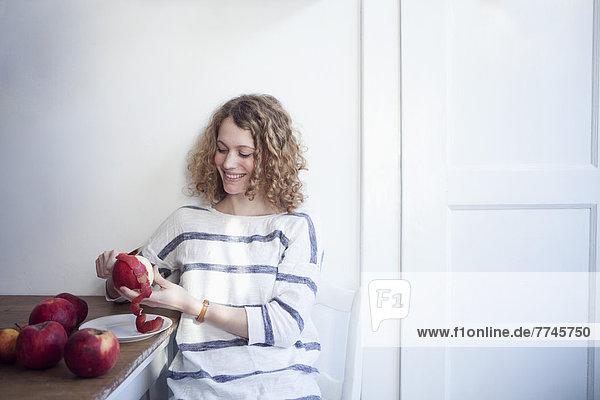 Junge Frau am Tisch sitzend und Äpfel schälend  lächelnd