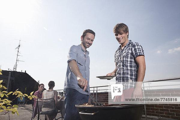 Männer grillen auf dem Grill  lächelnd