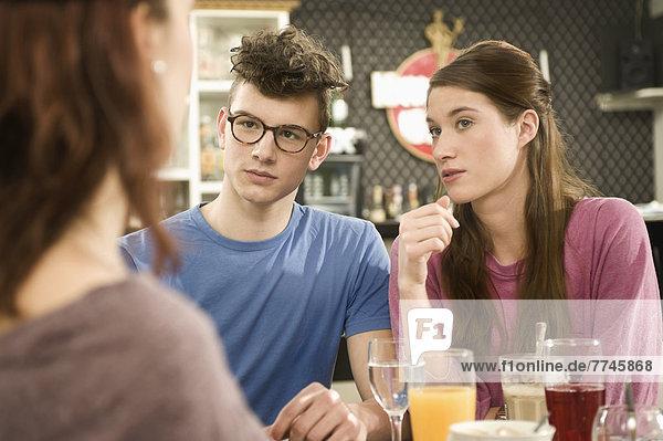 Deutschland,  Bayern,  München,  Junge Freunde beim Streit im Café