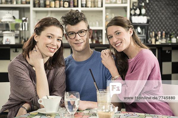 Deutschland  Bayern  München  Portrait junger Freunde im Café  lächelnd