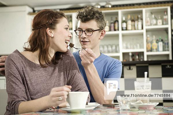 Junger Mann füttert Kuchenstück an Frau im Kuchen
