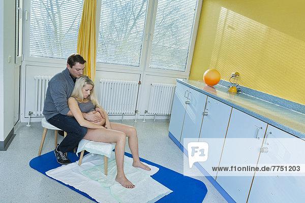 Mann und Frau im Kreißsaal während der Entbindung, die
